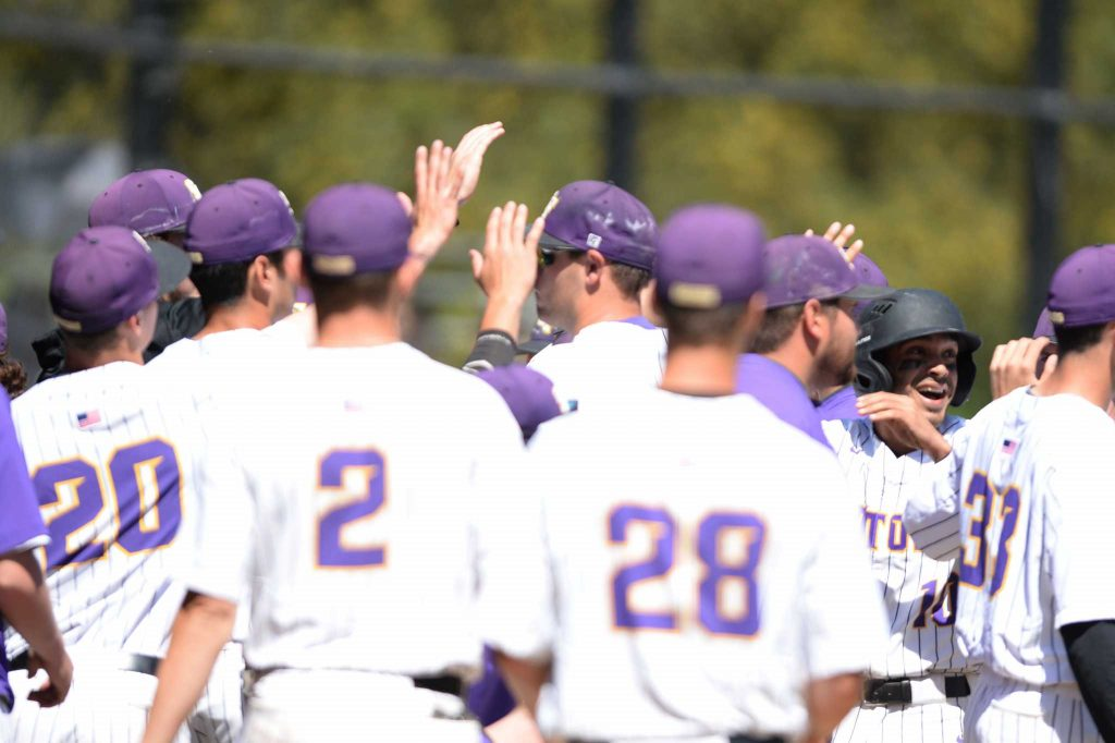 Gators outfielder Jacob Lopez (10 - far right) smiles as he high-fives his teammates during a baseball game between the SF State Gators and the Cal State San Bernardino Coyotes at Maloney Field at SF State on Saturday, Apr. 1, 2017 (Aaron Levy-Wolins/Xpress).