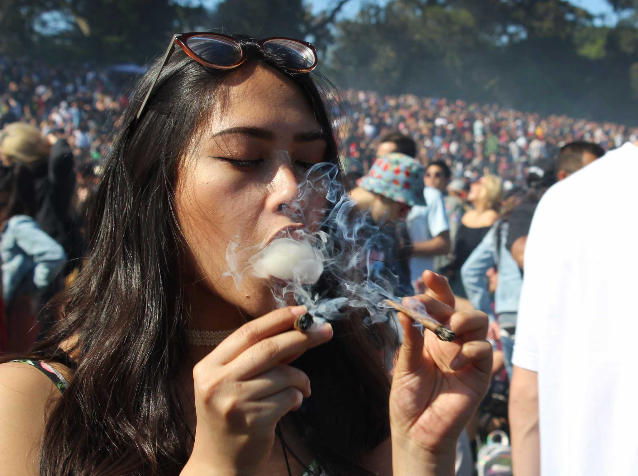 Le'alana Newman hits two blunts at exactly 4:20 p.m. at the city-permitted 420 celebration at Hippie Hill in San Francisco, Calif. on April 20, 2017 (Xpress/MJ Ongoy).