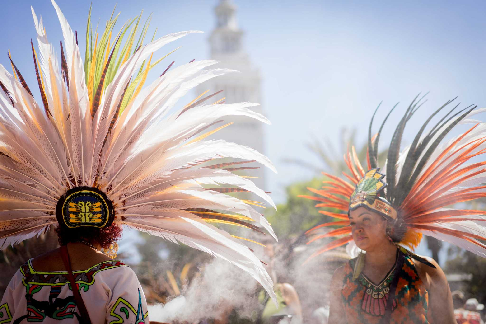 Maya Ponce (right) speaks with a fellow traditional Aztec dancer from the Xiuhcoatl group at the May Day protest down Embarcadero Street on Monday, May 1, 2017. (Sarahbeth Maney/Xpress).