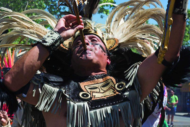 Alvaro Tellez plays music with a carrizo, an Aztec flute, while performing Aztec traditional dance to bless the May Day March in Oakland, Calif. on Monday, May 1, 2017. (Lee Kin/Xpress)