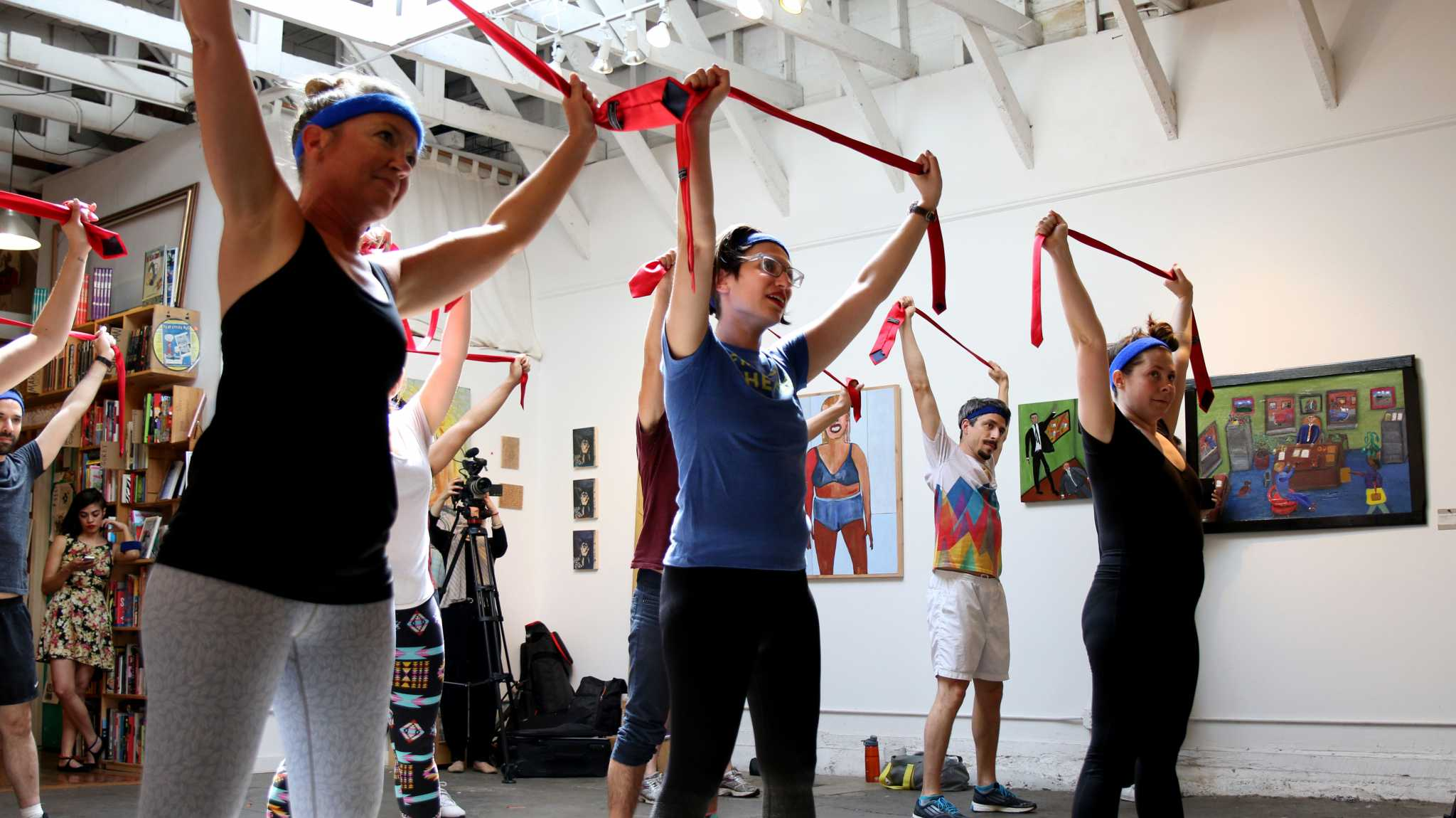 Anti Trump Aerobic class participants stretching with ties at Alley Cat Bookstore in SF on April.30, 2017 (Kyler Knox/Xpress)