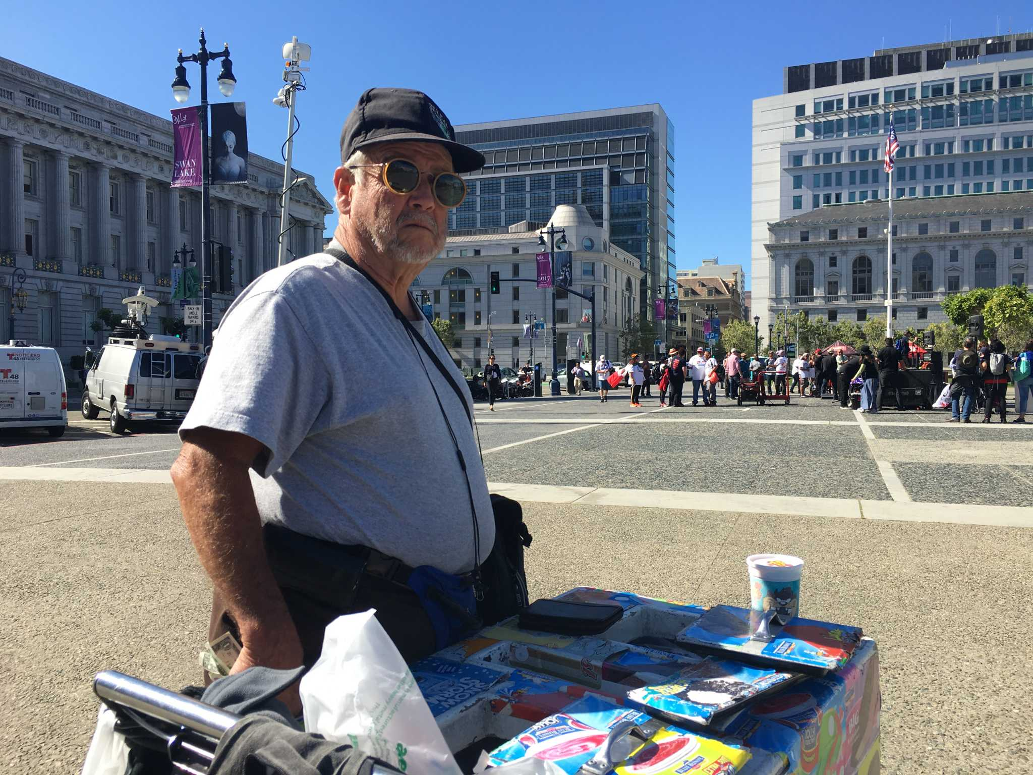 Ramiro Gutierrez Ortiz, 75, stands next to the 'A Day Without Immigrants' protest in front of City Hall with his ice cream cart on May 1, 2017. (Gracie Ngo)