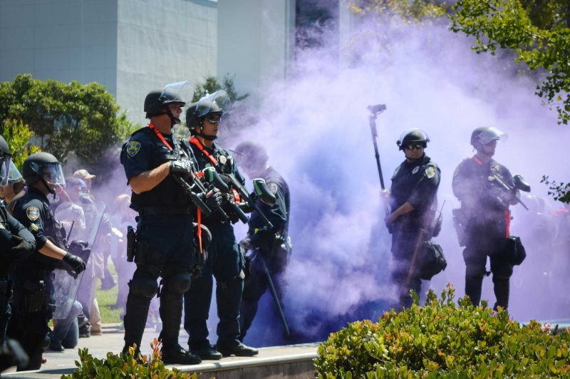 Protesters throw a smoke bomb at officers during the