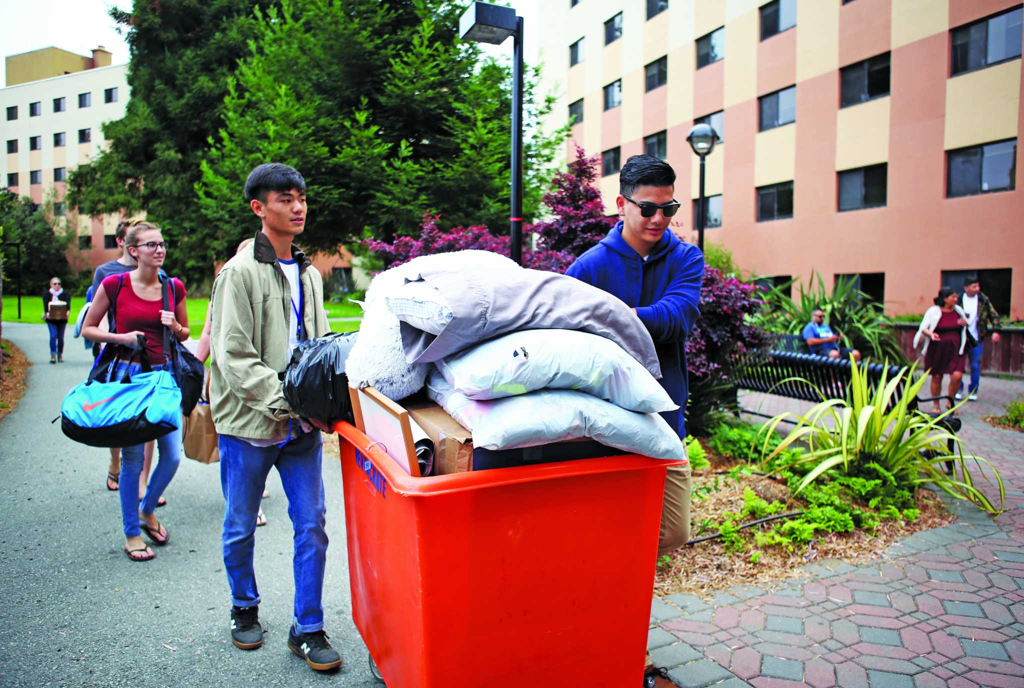 People move a cart into Mary Park Hall during freshmen move-in day at San Francisco State on Saturday, August 19, 2017. (Mira Laing/Golden Gate Xpress)