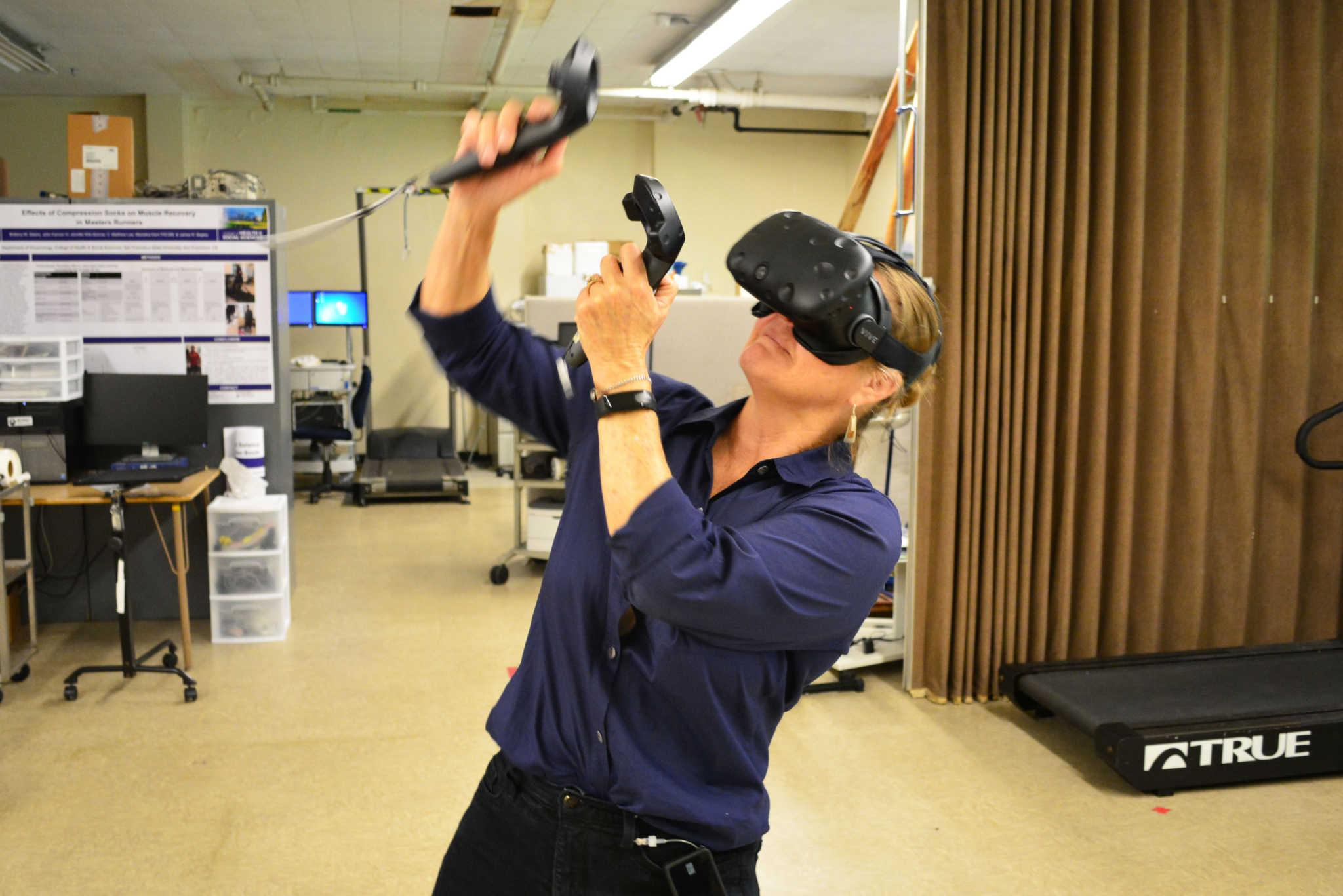 Professor Marialice Kern boxes with a virtual reality device in the Gym SF State on Monday, September 4, 2017. (Bryan Ramirez/Golden Gate Xpress)