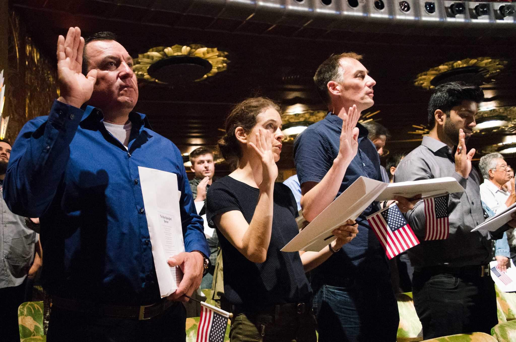 New citizens take an oath of allegiance during Register New Citizens to Vote hosted by Democracy Action at Paramount Theatre in Oakland on Thursday, September 7, 2017. (Richard Lomibao/Golden Gate Xpress)
