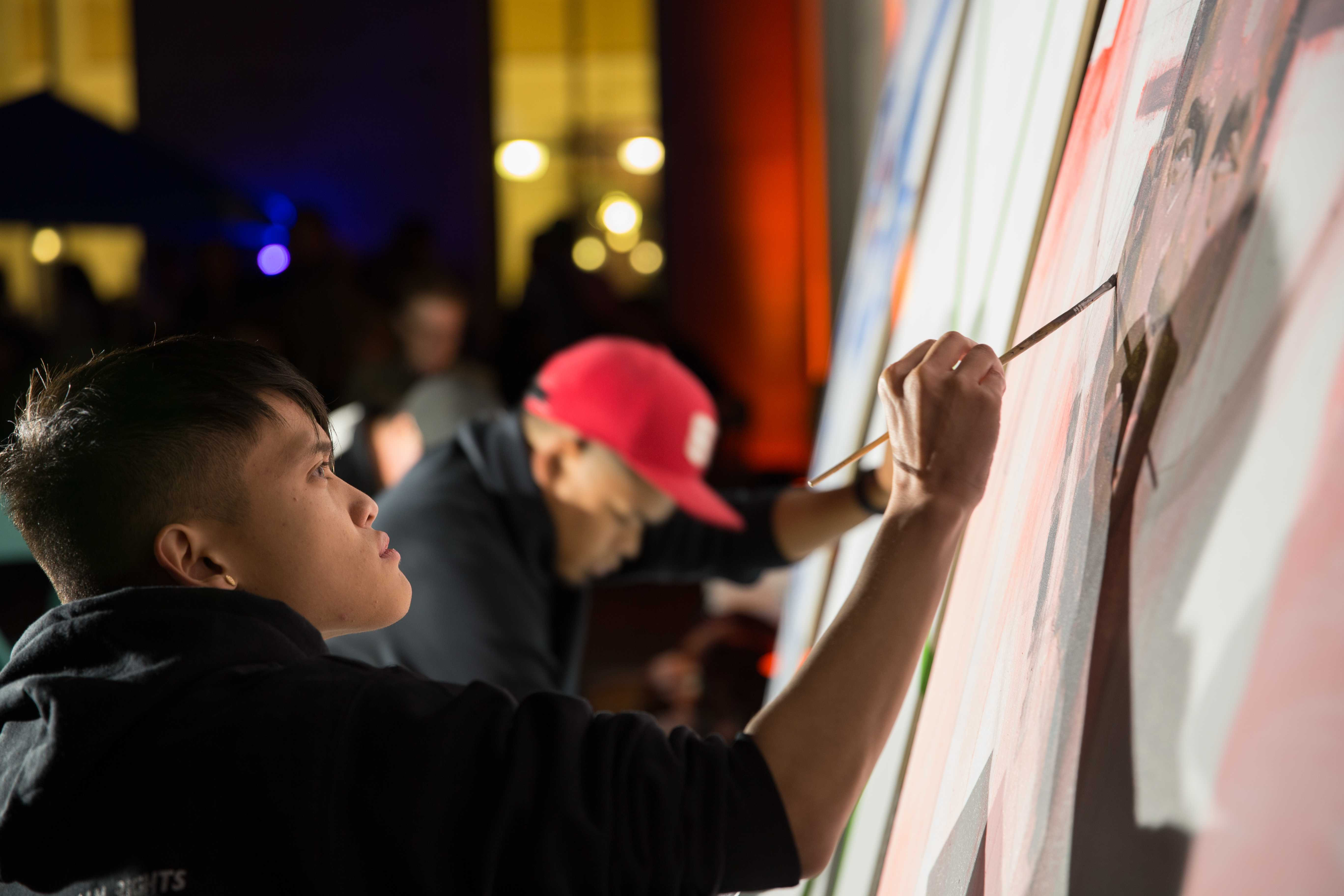 Ben Yu paints a portrait of Larry Itliong in the San Francisco Mint at Undiscovered SF in San Francisco on Friday, Oct. 20, 2017. (Travis Wesley/Golden Gate Xpress)