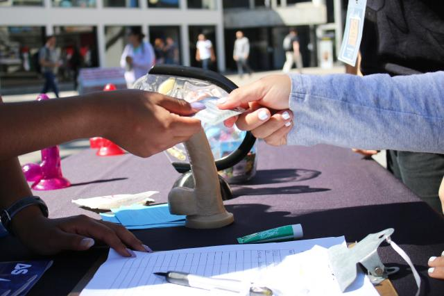 A person at the EROS booth hands out free condoms near the Cesar Chavez building at SF State, Wednesday, Sept. 27, 2017. (Laila Rashada/Golden Gate Xpress)