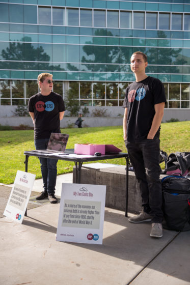 Nathan Bowman and Jordan Kenny from the Up to Us competition stand ready to speak with students about the national debt at SF State on Friday, Oct. 20, 2017. Up to Us is a student activist competition striving to raise awareness of the national debt, with a focus on finding nonpartisan solutions. (Travis Wesley/Golden Gate Xpress)
