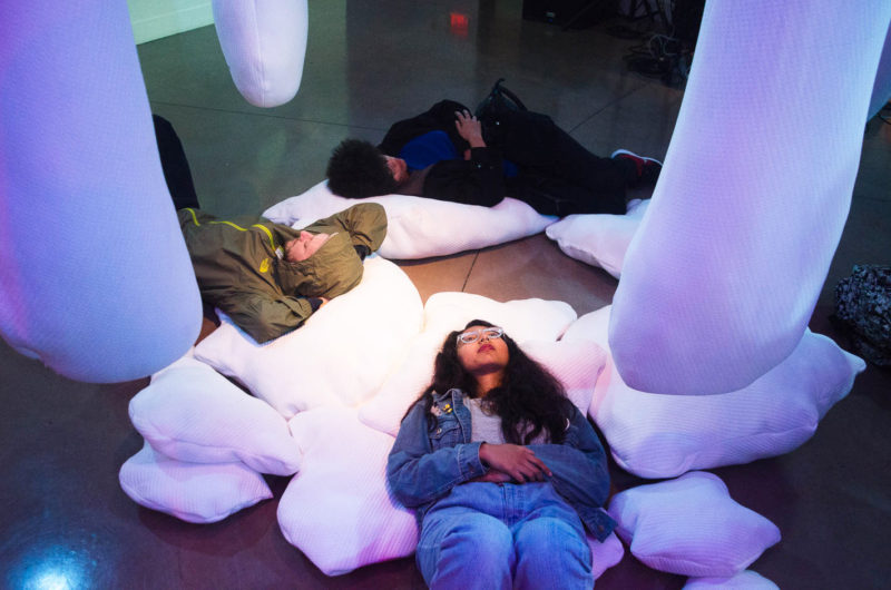 """Students lay on pillows part of an installation called """"Serotonin"""" at the opening reception for Macro Waves' NVM Gallery at SF State on Monday, October 19, 2017. (Richard Lomibao/Golden Gate Xpress)"""
