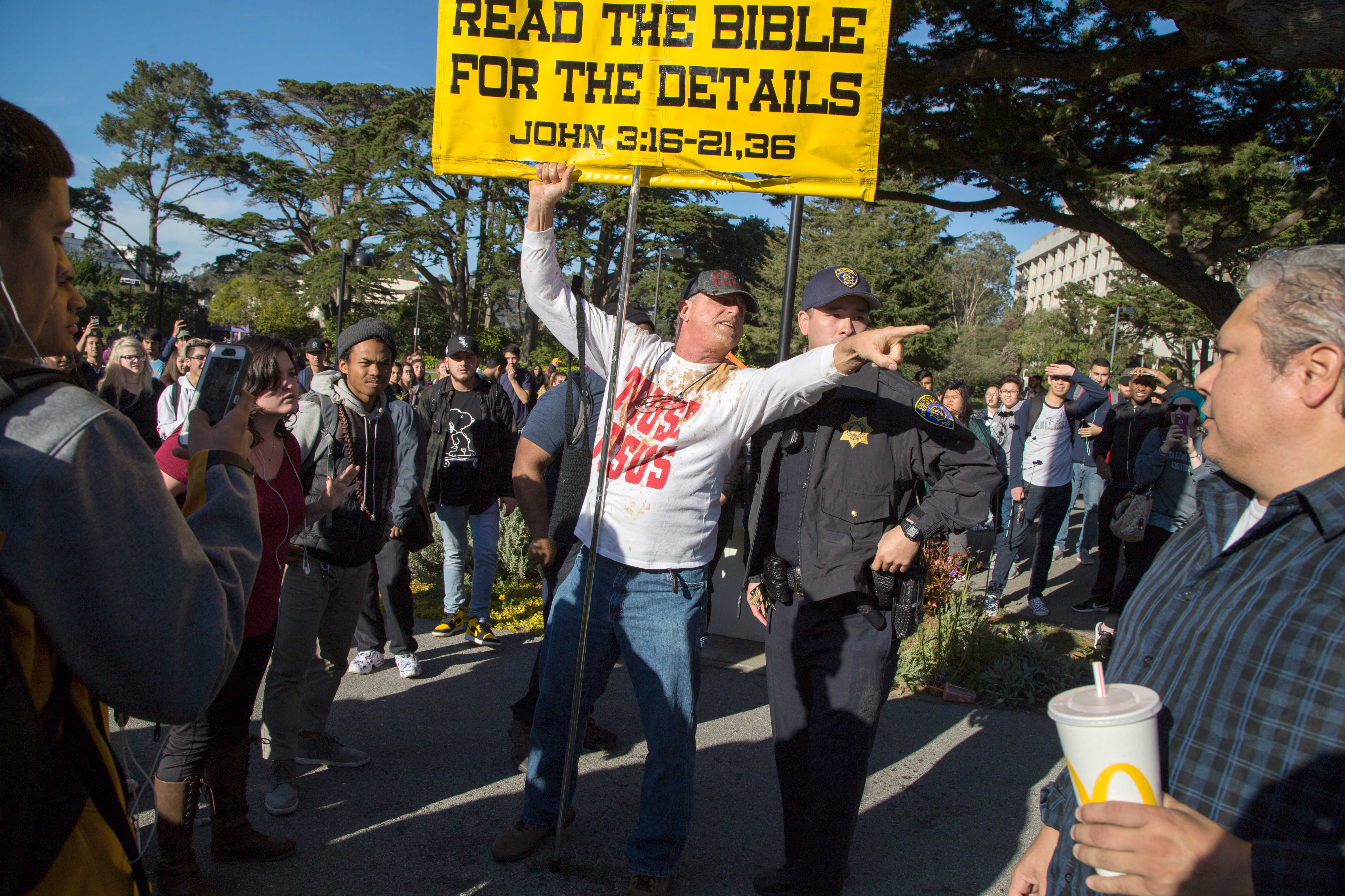 A religious activist speaks to a campus police officer following a physical altercation with students on campus at SF State on Wednesday, Nov. 29, 2017. (Travis Wesley/Golden Gate Xpress)