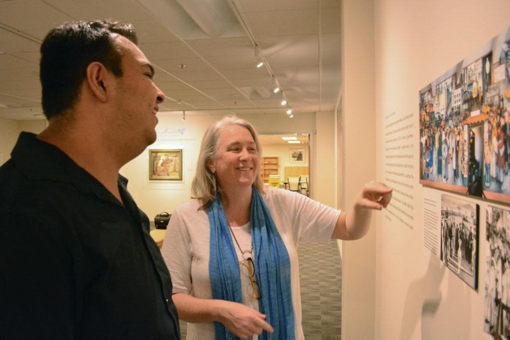 Exhibit director, Catherine Powell gives a tour to SF State alumni, Jose Oceguera at the Victor Arnautoff and the Politics of Art exhibit in J. Paul Leonard Library at SF State on Monday, Oct. 23, 2017. (Bryan Ramirez/Golden Gate Xpress)