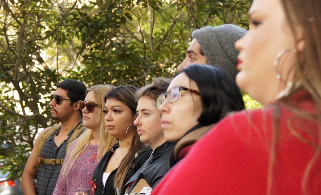 Participants of a campus vigil listen to  Dr. Christopher Carrington's talk at the AIDS Memorial Grove at SF State on Friday, Dec. 1, 2017. (Aya Yoshida/Golden Gate Xpress)