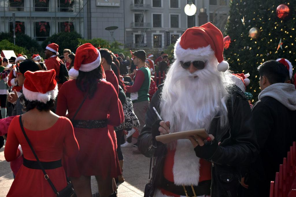 Cyrus, who calls himself Rock N' Roll Santa, sketches out a portrait of another Santa Claus during SantaCon 2017 in San Francisco, Saturday, Dec. 09, 2017. (Garrett Bergthold / Golden Gate Xpress)