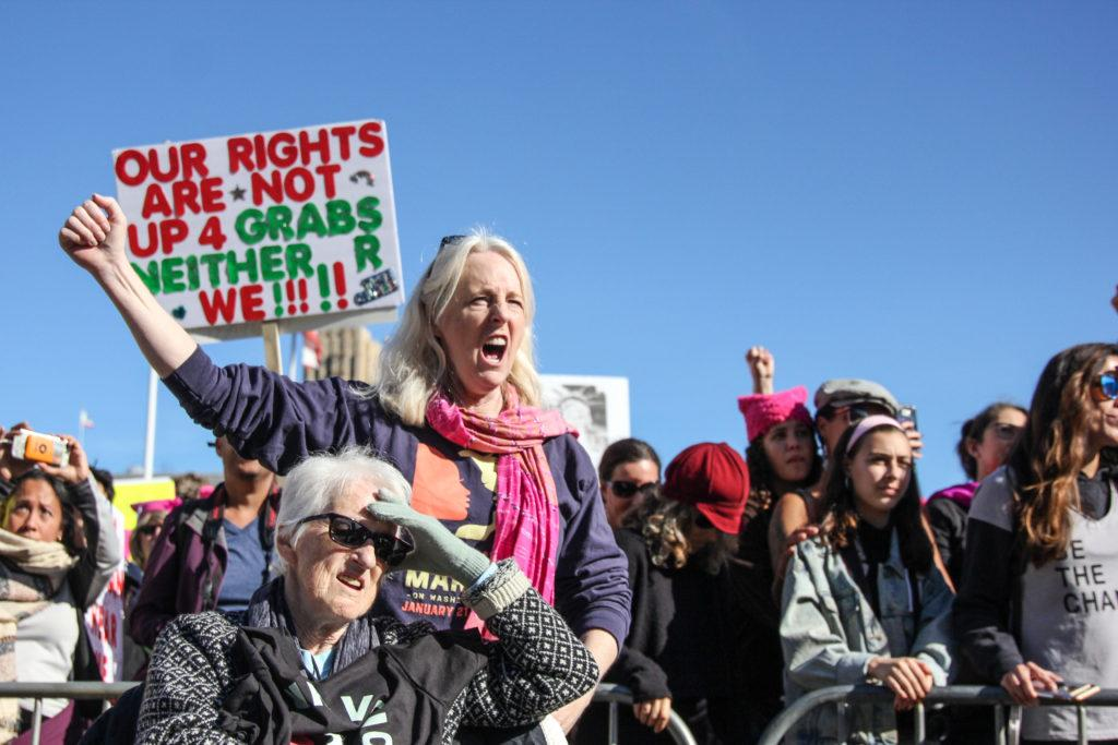 Karen Alexander, 57, and her mother Betty Alexander, 82, listen to Sadali King's speech outside of Civic Center Plaza during the Women's March