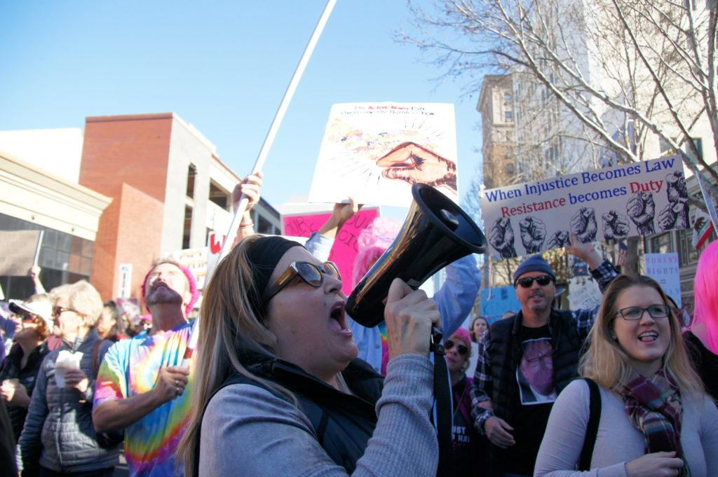 A woman leads participants of Women's March 2018 in San Jose by saying