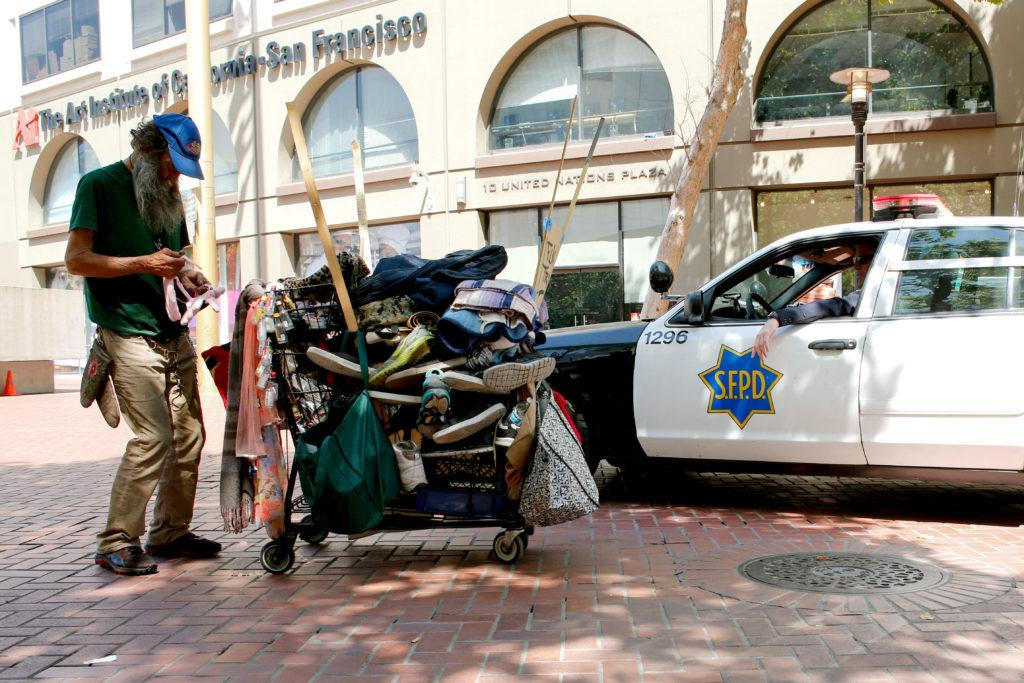 A man pushes a cart full of his belongings through the United Nations Plaza as San Francisco Police Officers clear the area for the Heart of the City Farmers Market on Saturday May 6, 2017. (Niko LaBarbera/Golden Gate Xpress)