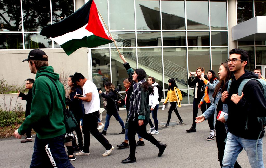 A student holds the Palestinian flag while a student rally crosses the San Francisco State campus in San Francisco, Calif. on Feb. 28, 2018. (Janett Perez/Xpress)