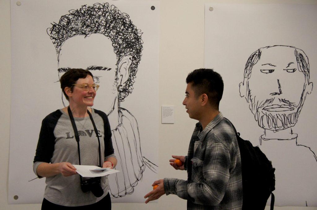 A derector of A People's Museum of LGBTQ History, left, and visual communication major Nick Corona, right, enjoy talking during the opening reception at SF State on Thursday, Feb. 15, 2018. (Aya Yoshida/Golden Gate Xpress)