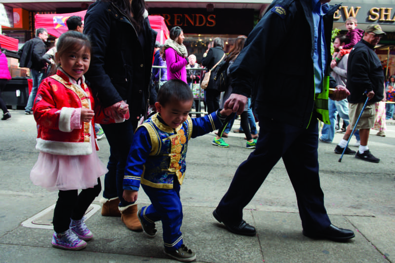 Katelyn Luong, left, and Jacob Luong, right, walk hand in hand with their parents through Chinatown as the city begins to prepare for the Chinese Lunar New Year Parade on Saturday Feb. 24, 2018 in San Francisco. (David Rodriguez/Golden Gate Xpress)