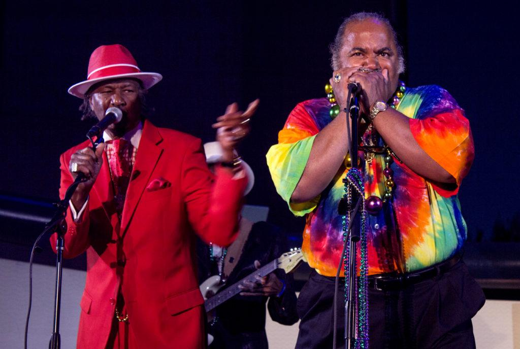 (Left to Right) Fillmore Slim guest sings alongside Silver Fox who is playing the Harmonica at the 12th annual Mardi Gras celebration at the Fillmore Center Plaza on Feb. 13, 2018. (Jordi Molina/Golden Gate Xpress)