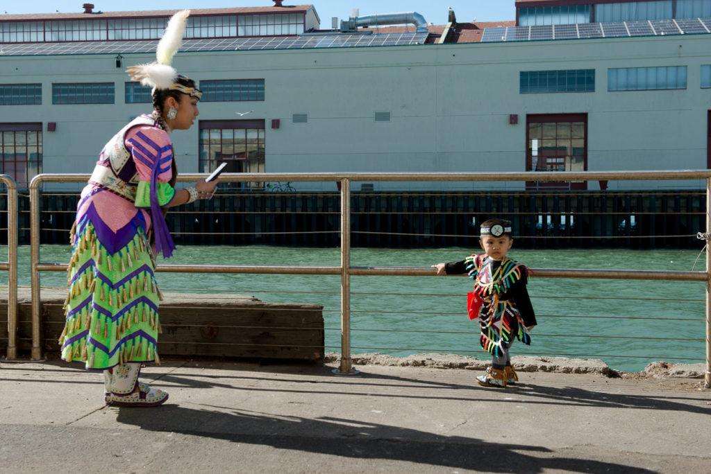 Celeste McGurk, left, takes photo of her 2-year-old son, Jaycen Llena, on the side of the Fort Mason Center in his cultural attire during the 2018 Two-Spirit POWWOW held at Fort Mason Center in San Francisco on Saturday, Feb. 3, 2018. (David M. Rodriguez/Golden Gate Xpress)