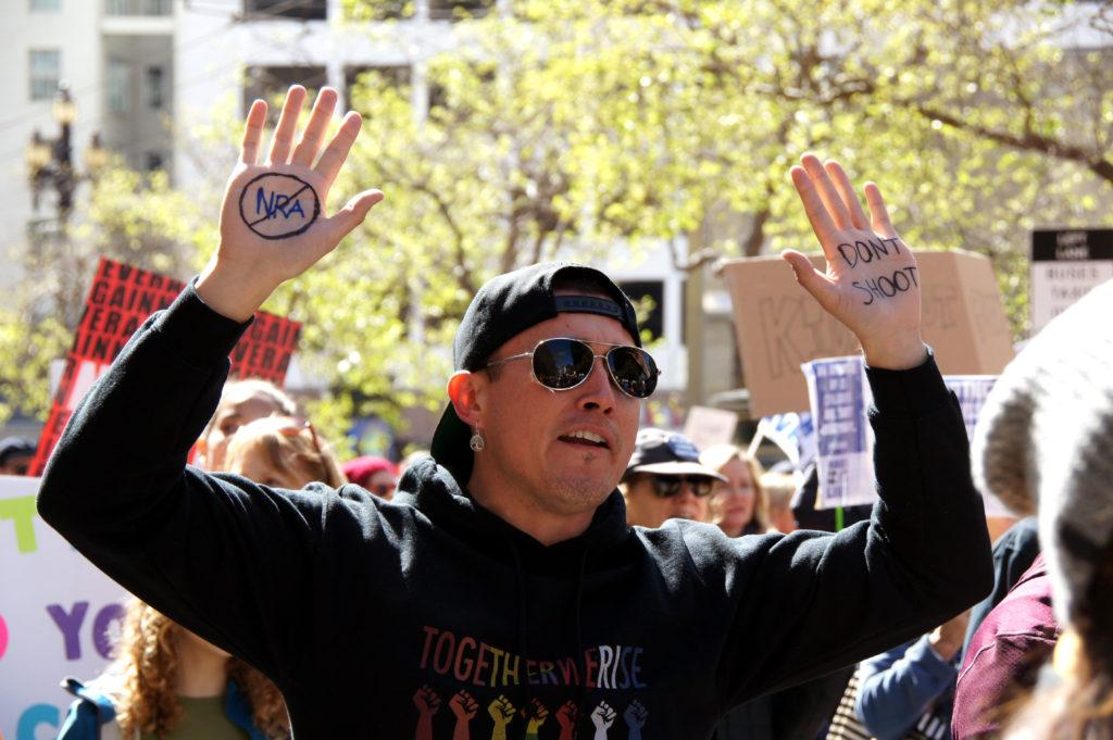 Percy Castellanos hands up and marching on San Francisco's Market Street against gun violence on Saturday, March 24, 2018. (Aya Yoshida / Golden Gate Xpress)