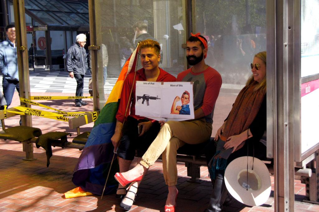 Immigrants from Iran Francisco Presly, lest, and Sam Soda, right, sit on MUNI bus stop during the march for out lives in San Francisco on Saturday, March 24, 2018. (Aya Yoshida / Golden Gate Xpress)