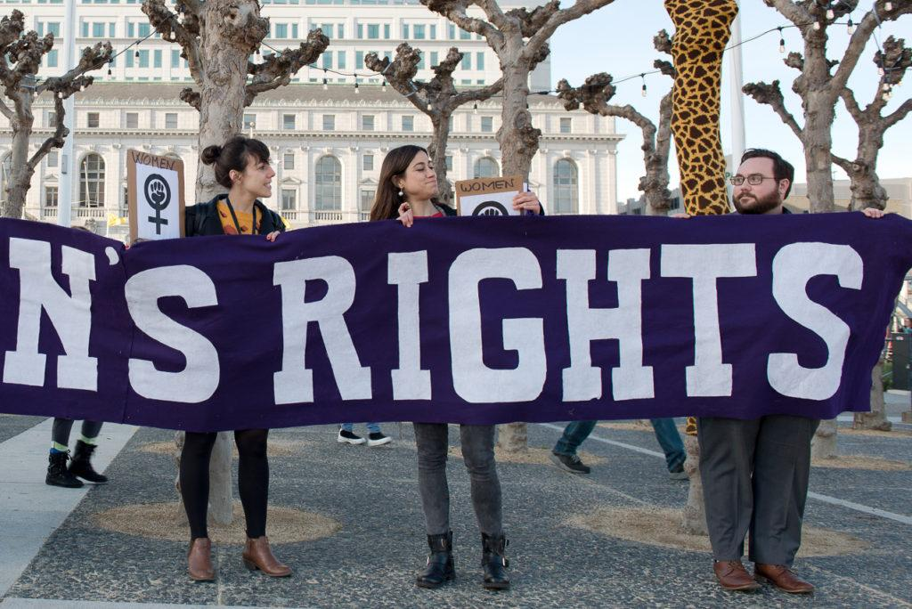 Carolina Alquezar, left, and Olatz Arteaga, center, protest against women's inequality around the world by holding a banner that read as