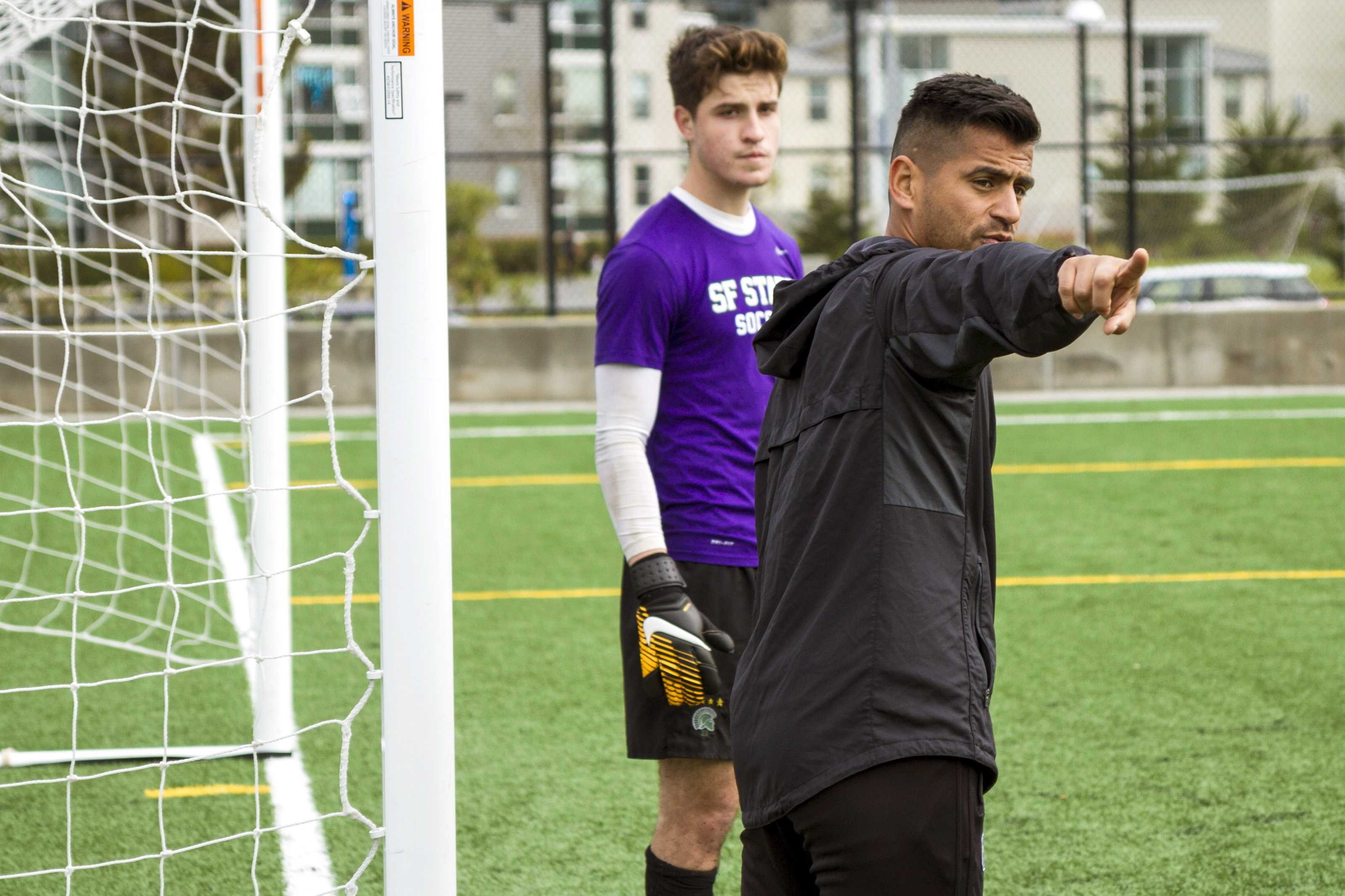 Head Coach Javier Ayala-Hil,right, works with goalkeeper Erik Ornelas, left, in between corner kicks at the Men's Soccer practice at SF State on Friday, Mar. 2, 2018. (Joey Vangsness/Golden Gate Xpress)