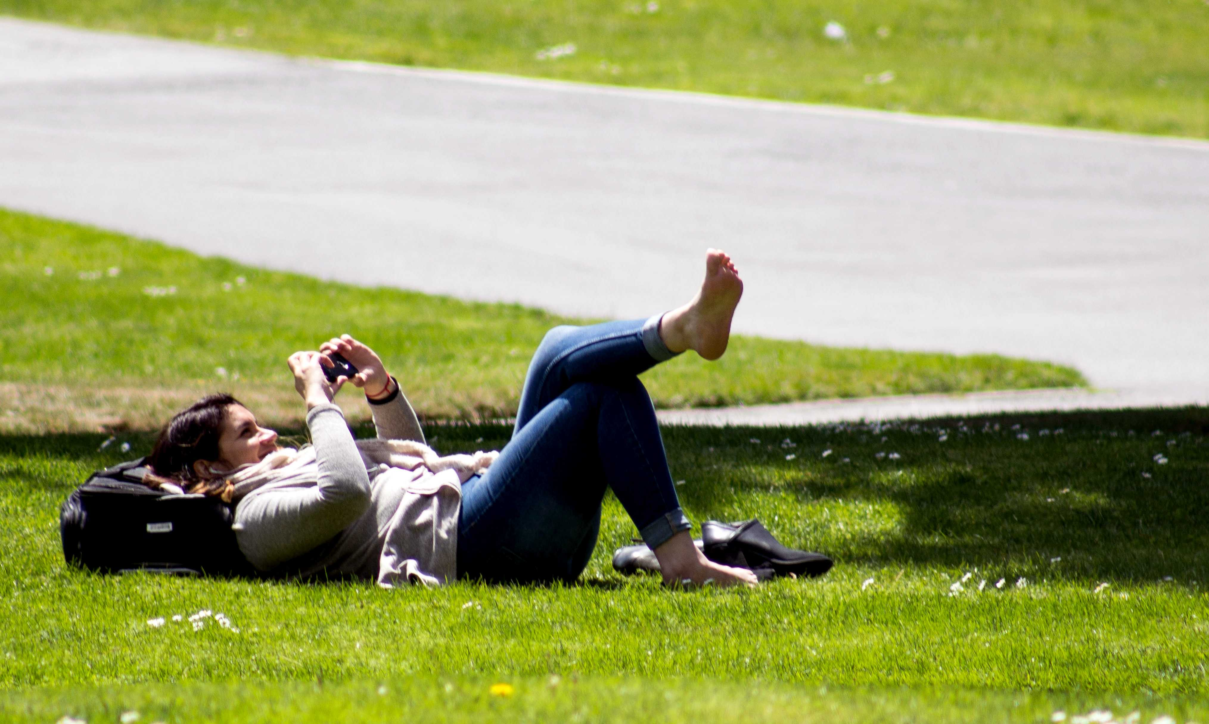 A SFSU student uses their phone on a sunny day while laying on the grass. Photo by Jordi Molina