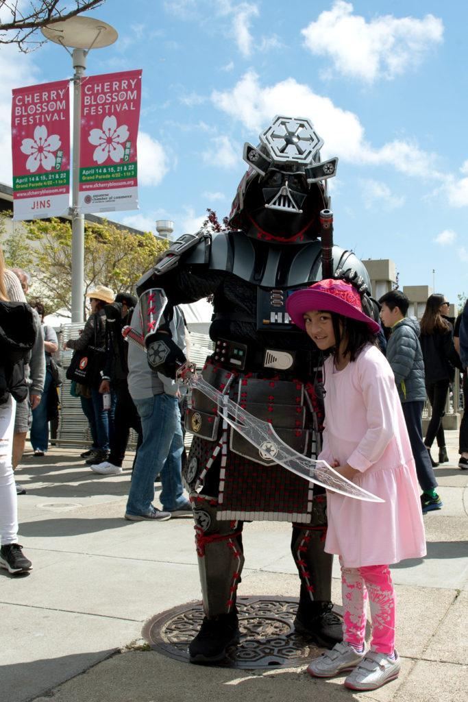 A young girl, photographs herself next to a Samurai as the 2018 Northern California Cherry Blossom in San Francisco comes to an end on Saturday, Apr. 15, 2010. (David Rodriguez/Golden Gate Xpress)