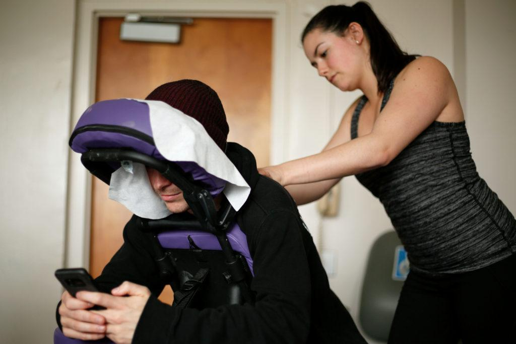 Jason Martin relaxes at SF State's Holistic Health Center while Siera Hinkle massages his shoulder muscles on Wednesday, March 14, 2018. SF State's Holistic Health Center provides free massages every Wednesday in HSS 329 as a resource for students to help alleviate stress. (Niko LaBarbera/Golden Gate Xpress)