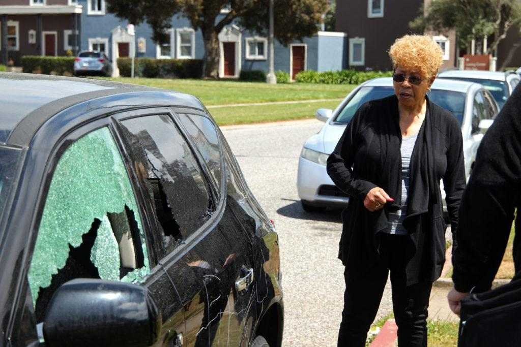 Hazel Jackson, a Parkmerced resident, inspects her vandalized car at Juan Bautista Circle near Fuente Avenue in the Parkmerced neighborhood close to SF State on Wednesday, May 16, 2018. The act of destruction seems to be racially motivated.  (Christian Urrutia/ Golden Gate Xpress)