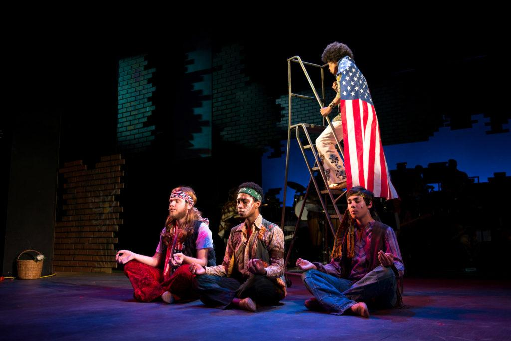 Neil Munz, left, Keishaun Burroughs, middle, Christian Cantrell, right, all sit down in relaxing yoga poses while Nick Christman walks up the stairs wearing an American flag around his neck during rehearsals for the upcoming