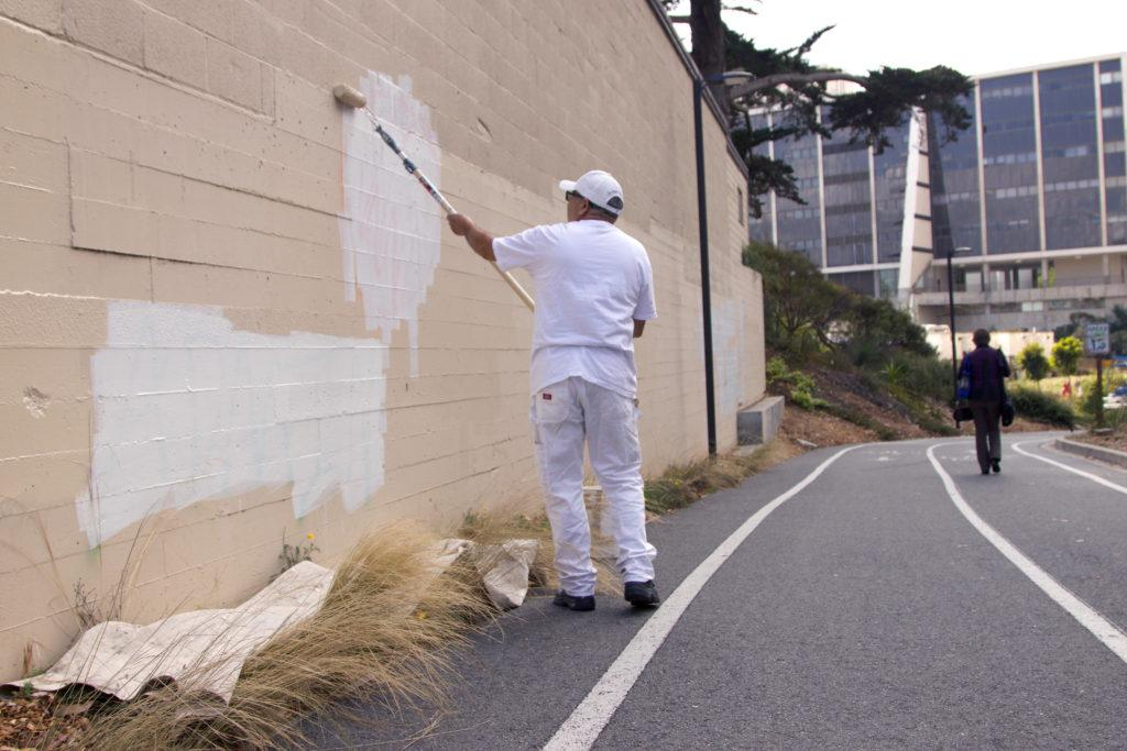Sergio H. paints over graffiti on a wall near a walkway toward University Park North at SF State on Aug. 29, 2018. (GoldenGateXpress/Oscar Rendon)
