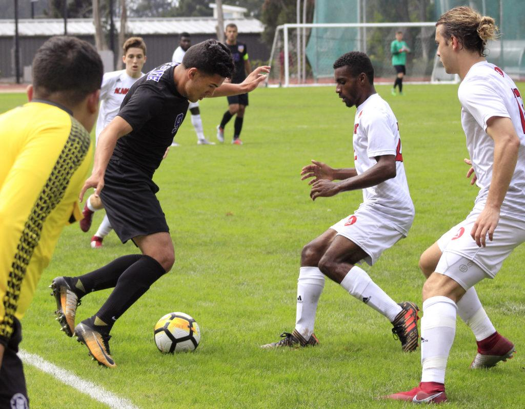 SF State player Feliciano Cardenas dribbles the ball through two Academy of Art players in their game against each other on Thursday, Aug. 30, 2018. (GoldenGateXpress/Lindsey Moore)