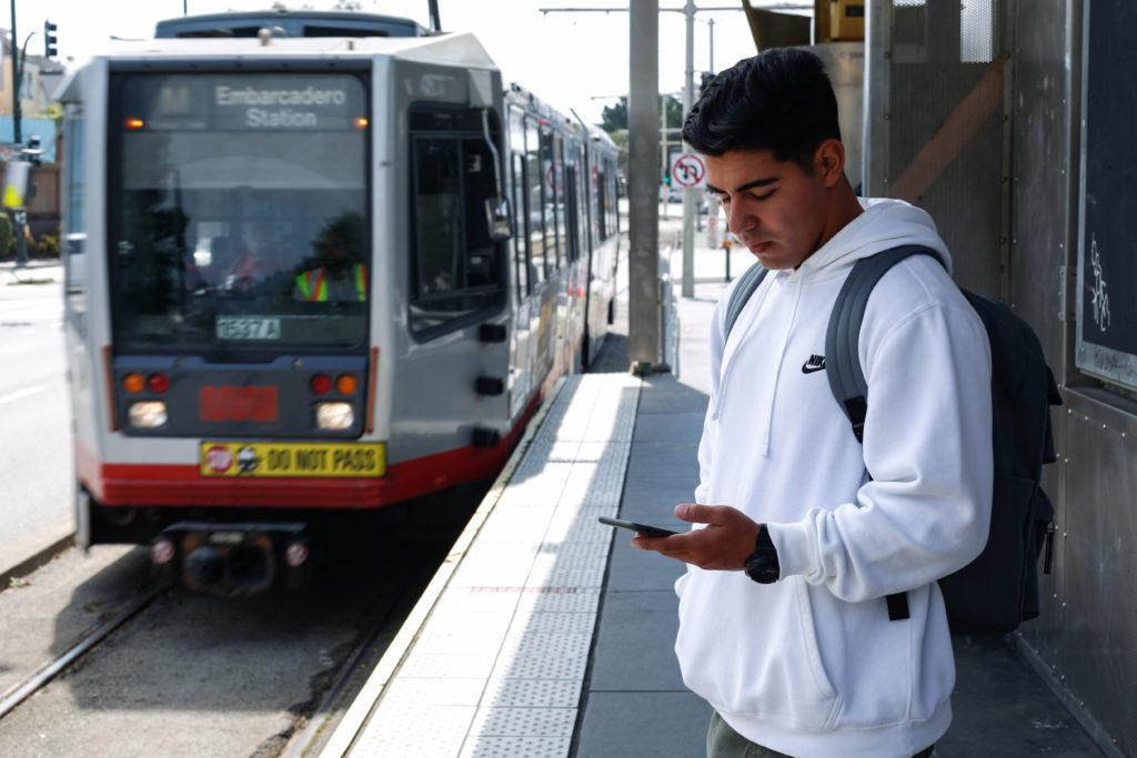 Computer Science major Anthony Rodriguez looks at his phone while the Muni M line train approaches 19th and Holloway during the first day of classes at SF State on August 27, 2018. (Niko LaBarbera/Golden Gate Xpress)