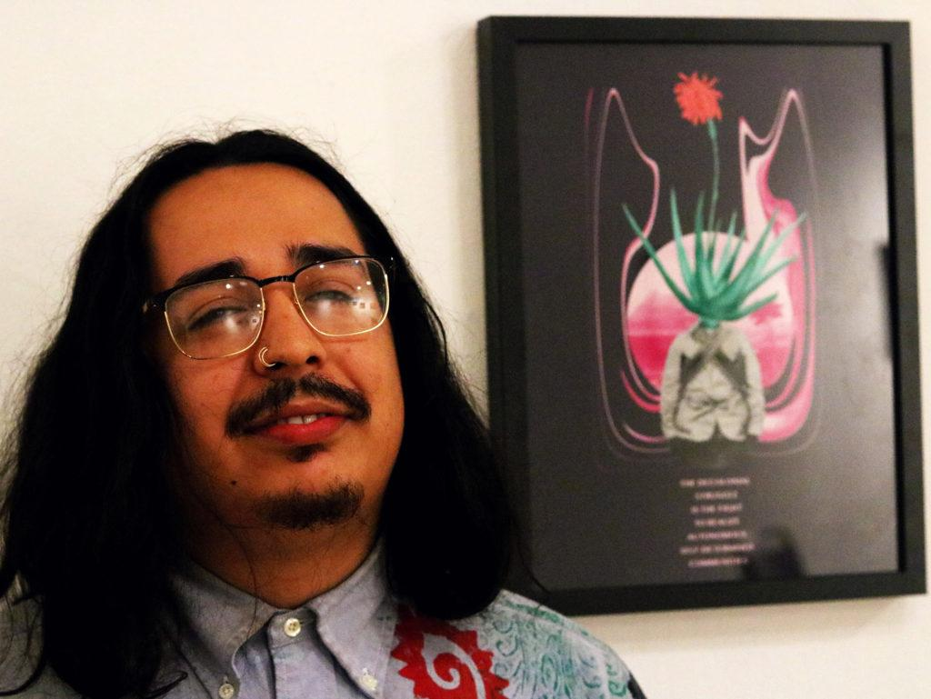 "Chris ""L7"" Cuadrado poses for a portrait at the Art Gallery in the Caesar Chavez Student Center at SF State on Sept. 6, 2018. Cuadrado's art is known for informing communities about resistance. Cuadrado's art is in this picture is a message-based collage involving decolonization, oppression, and liberation through the act of resistance. (Evan Moses/Golden Gate Xpress)"