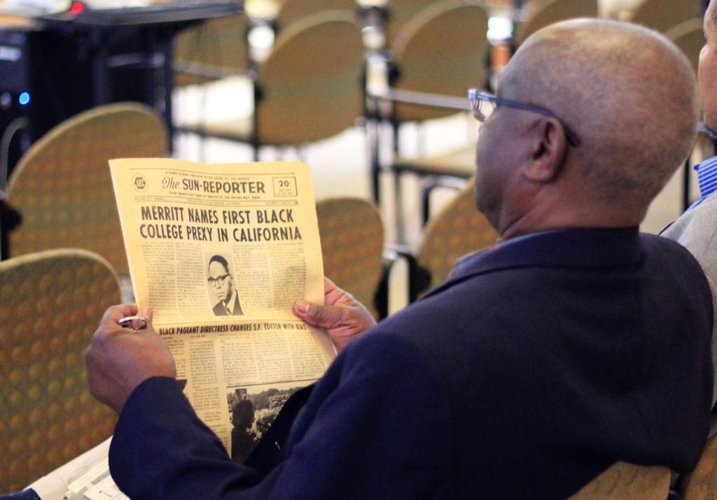 James Paul Garrett reads an old newspaper about the first black college president while he waits for the 50th anniversary panel, discussing the first SF State Black Student Union at the African American Museum and Library in Oakland on Saturday, Sept. 15. (Lindsey Moore/Golden Gate Xpress)