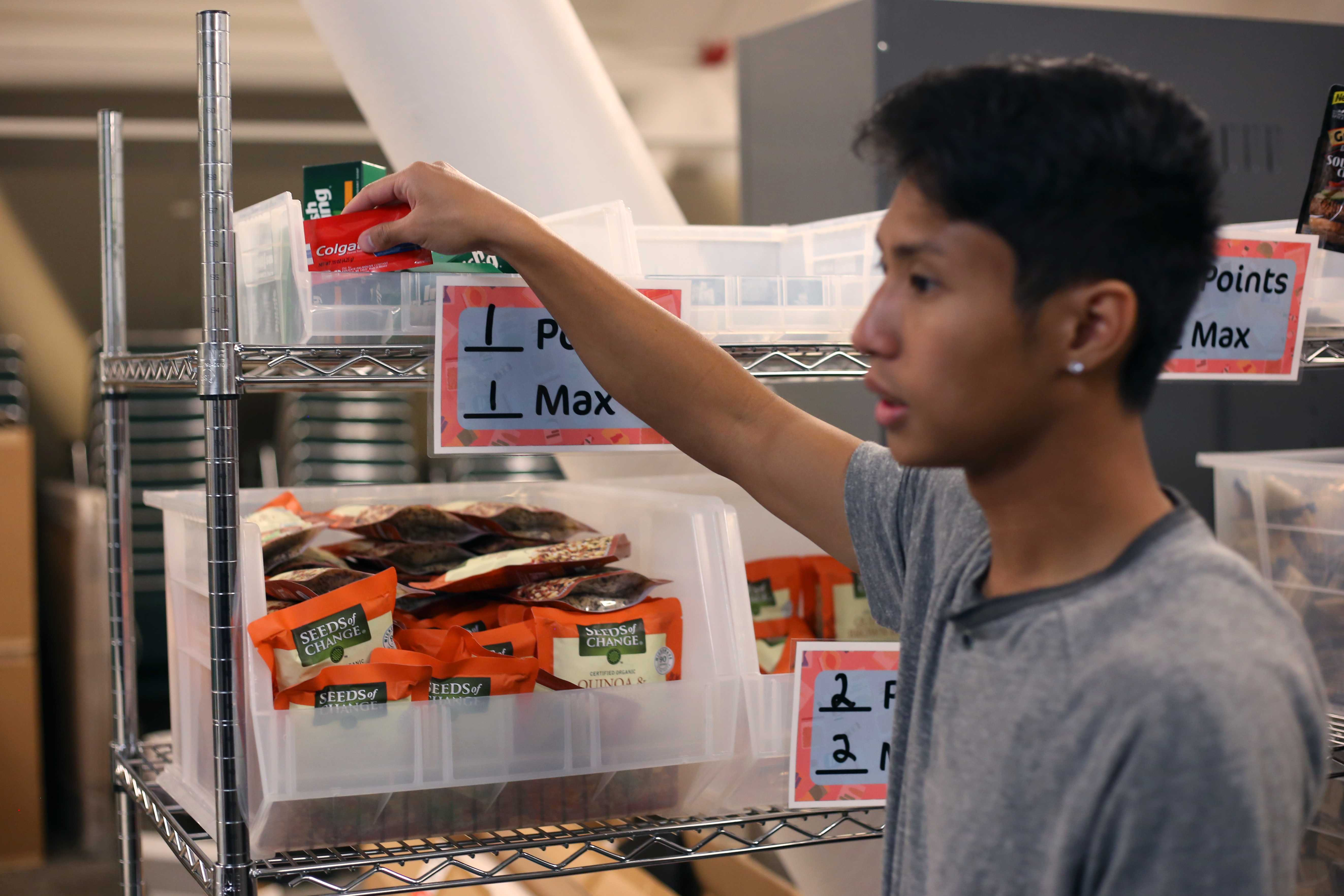 Asian American studies major Nathaniel Roque picks up a towelette in the Pyramid room where the food cupboard is held, next to the Jack Adams Hall in the Cesar Chavez Student Center on Wednesday, Sept. 19. (Christian Urrutia/Golden Gate Xpress)