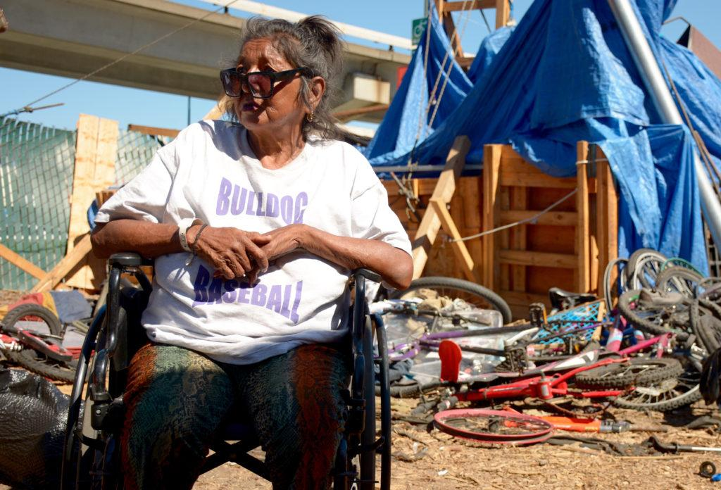 Barbara Verduzco sits outside her tiny home, which was unscathed by the fire that burned down one third of the encampment in Oakland on Saturday, Sept. 15, 2018.
