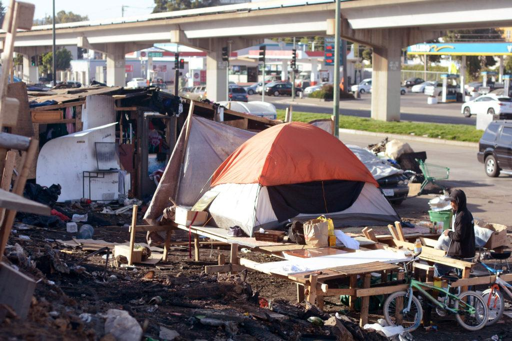 A man sits in a homeless encampment in Oakland, Calif., on Thursday, Sept. 13, 2018. A fire burned nearly one third of the encampment early Tuesday morning.