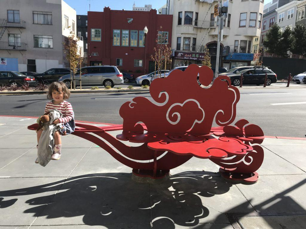 Ramona Arcega, daughter of Professor Michael Arcega, sits on one of the benches from the installation series titled Auspicious Clouds | Heavy Fog at Broadway near Columbus Avenue in Chinatown on Monday, Sept. 23. (Courtesy of Professor Michael Arcega)