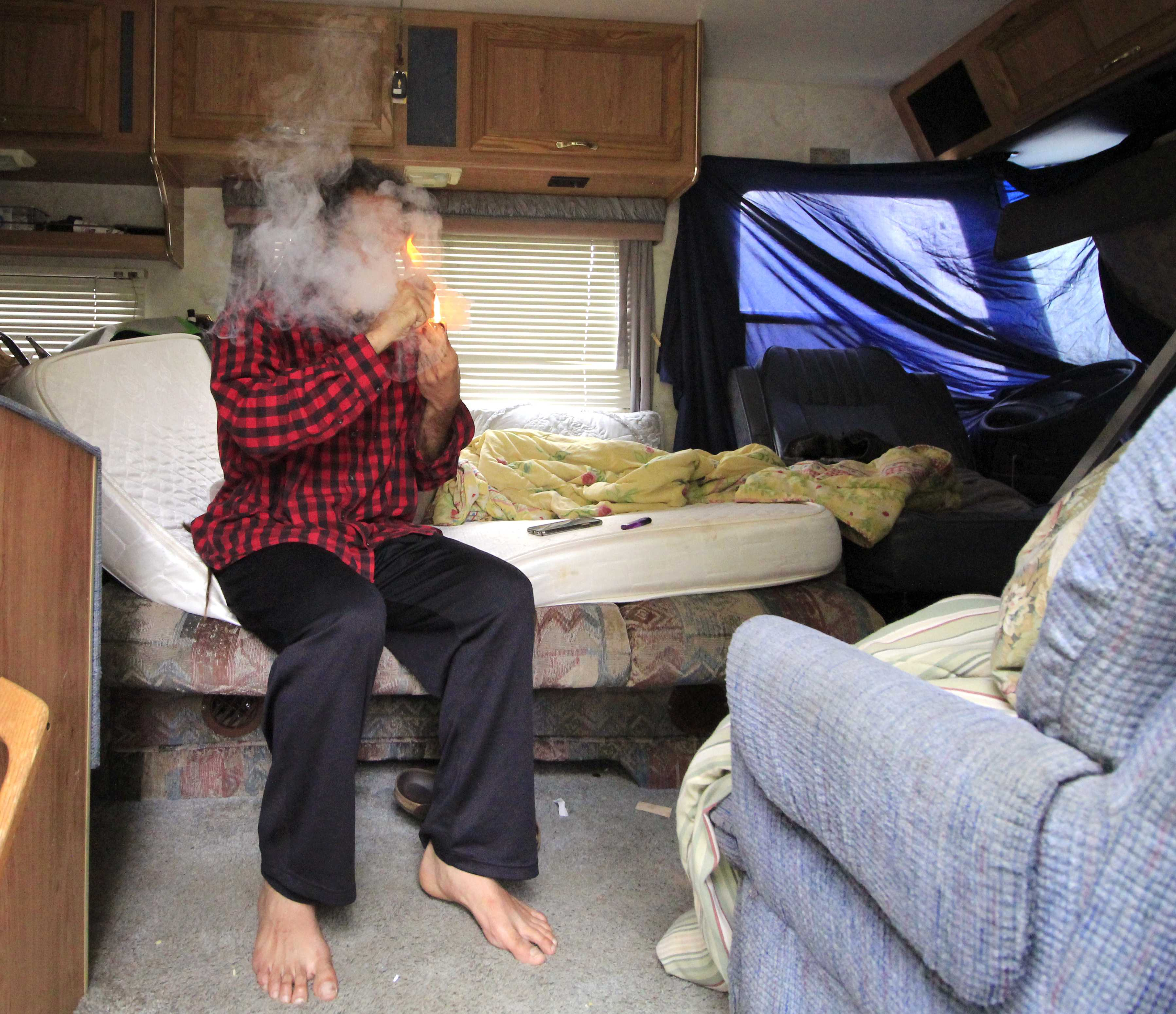 Juan Martinez, who moved to San Francisco from Brazil, smokes cannabis inside his motorhome parked on Lake Merced Boulevard on Monday, Sept. 3. Martinez is one of many who are living out of their vehicles, either by choice or who are forced to, because of the lack of affordable housing in the Bay Area. (Lindsey Moore/Golden Gate Xpress)