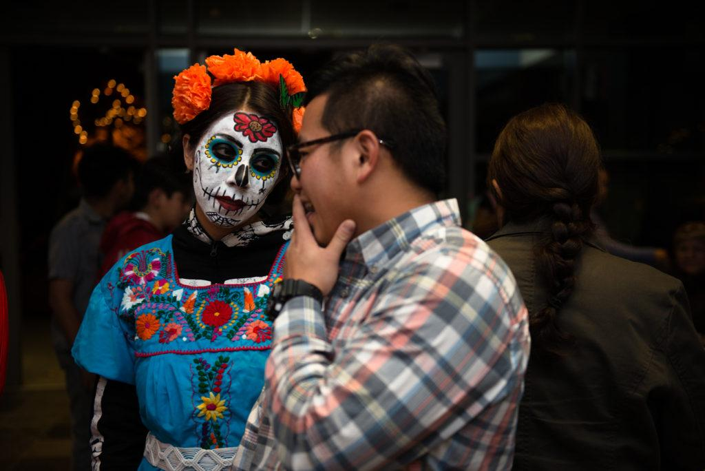 A young couple listens to the music and absorbs everything that is happening around them, and embraces the culture by not only dressing in a traditional way, but also by making herself appear as a skull for the Day of the Dead in Salinas, Calif. Photo taken on Nov. 01, 2017 by David  Rodriguez Photojournalism Student at SF State.