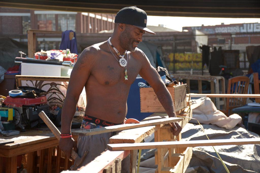 Fred Smith rebuilds his home after the encampment fire damaged his surrounding community on E 12th Street in downtown Oakland on Saturday, Sept. 22. (Tristen Rowean/Golden Gate Xpress)