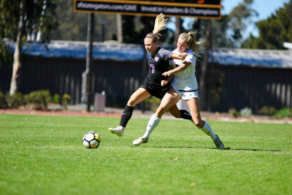 Gator defender Kylie Schneider and Triton defender Ashlynn Kolarik fight for the ball at the Women's Soccer match between SF State and UC San Diego on Oct. 7, 2018. (Francisca Velasco/Golden Gate Xpress)