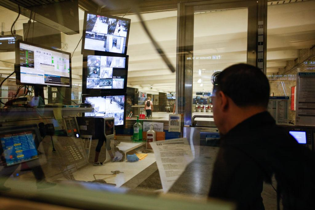 A Bart operator who refused to provide his name reviews a document from one of the multiple control rooms at the Civic Center Bart station while monitors pick up camera activity in the back on Saturday, Oct. 7, 2018. (Niko LaBarbera/Golden Gate Xpress)