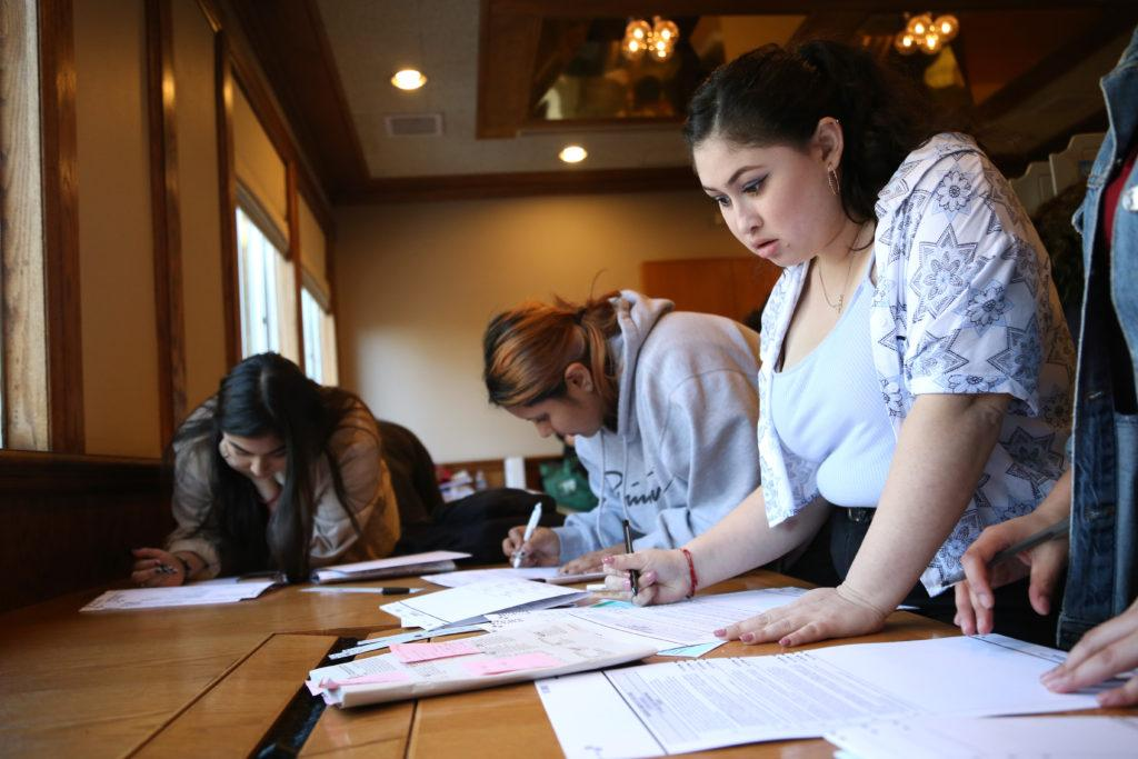 Brianna Galeas reads through ballot measures while voting in the Midterm Elections at SF State's Seven Hills Conference Center on Tuesday, Nov. 6, 2018. Some students waited in lines for three hours to cast their votes. (Mira Laing/Golden Gate Xpress)